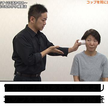 コップを耳に当てて聴力検査